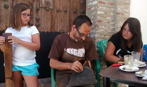 Fernando teaching handmade leather skills to his neices